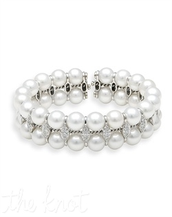 18k white gold bangle features vertical rows of pearls with marquis shaped clusters of round diamonds. Diamond TW: .85; 6&quot; expandable length; 3/4&quot; width. Rental jewelry.