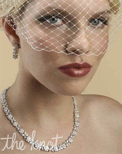 White or ivory birdcage veil features Russian netting.