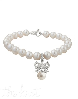 "From the Soft and Sophisticated Collection, this sterling silver bracelet features twenty-two 7mm freshwater pearls, white topaz and bow detail. 7-1/4"" L"