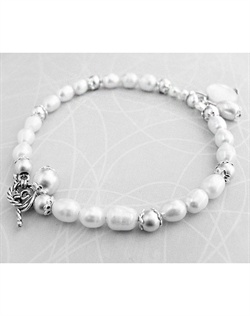 Bracelet features cultured freshwater pearls, sterling silver toggle closure, sterling silver matte and round silver beads, sterling silver floral accents and mother of pearl charm. 7 1/2""