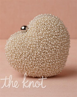 Pearl colored beaded heart clutch features silk, silver-plated brass, acrylic pearls and polyester lining. Also features hidden chain strap and snap closure.