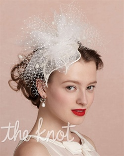 Ivory headpiece features polka-dotted and airy net tulle and sinamay petals.