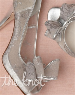 Silver nylon and leather pumps feature leather sole, metallic lace, and bow detail. Sizes 5-11