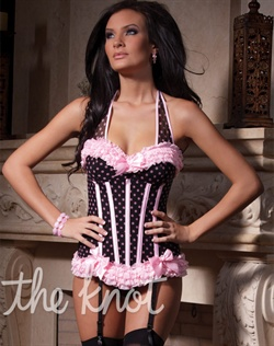 Black and pink polka dot mesh corset features padded cups, pink Lycra covered boning, pink ruffle mesh trim detail, hide-able halter straps, hook and eye back closure, detachable garter straps and pink satin bow details. Stockings, thong and ruffle panty not included.