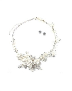 Set features rhodium finish, cubic zirconia, porcelain white flowers and freshwater pearls.