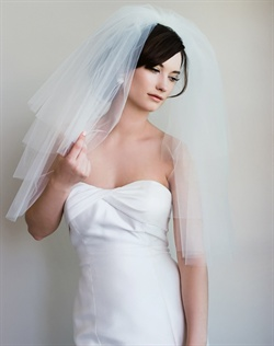 Elbow-length veil features four tiers, tulle and silver metal comb. Available in diamond white or ivory. Up to 40""