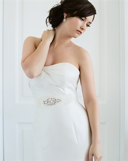 Sash features Alencon lace, satin ribbon, Swarovski rhinestones and freshwater pearls. Available in diamond white or pale ivory.