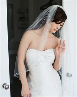 "Finger-tip length veil features tulle, Swarovski rhinestones and crystals, freshwater pearls and silver embroidery. Available in diamond white or ivory. 40"" L"