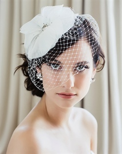 Fascinator features oversized tulle and silk organza flower, Swarovski rhinestones and French net face veil. Available in diamond white or pale ivory.