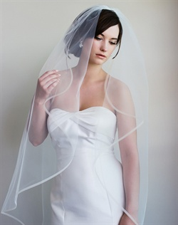 "Finger-tip length veil features tulle and crinoline trim. Available in diamond white or pale ivory. 20""-145"" L"