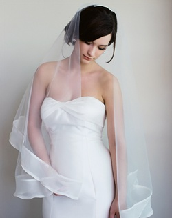 Finger-tip length veil features two tiers, silk organza folded trim and tulle.