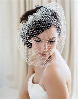 One of the most popular shapes, the Pout veil, now all glammed up in French net with a gorgeous silver filigree and Swarovski stone accent at the comb. Wear it over your face for the ceremony then flip it around for the reception--it's two in one!  Available in pale ivory, diamond white.