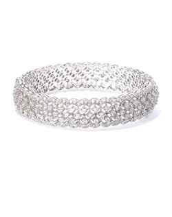 Vintage bangle graced with gentle scalloping adorned with round-cut cubic zirconia. Set in brass with rhodium plating (shown in silver finish).