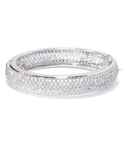 Classically styled bangle with a round contour and lavish arrangement of shimmering cubic zirconia. Set in brass with rhodium plating (shown in silver finish).