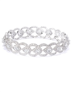 Classic bangle with interplay of shapes dotted with pavé cubic zirconia and man-made stones. Set in brass with rhodium plating (shown in silver finish).
