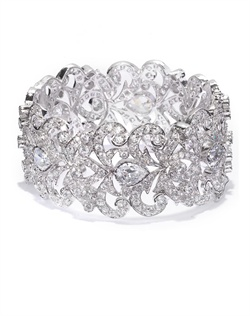 Classic styled bangle with an antique flair, crafted with open scrollwork, shimmering cubic zirconia insets and crystal briolette. Set in brass with rhodium plating (shown in silver finish).