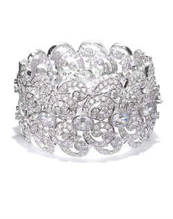 Elegant statement bangle styled with graceful open scrollwork, round-cut and oval crystals and cubic zirconia. Set in brass with rhodium plating (shown in silver finish).