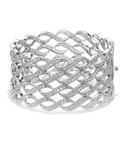 Classic cuff bangle graced with a series of pavé cubic swirls. Set in brass with rhodium plating (shown in silver finish).