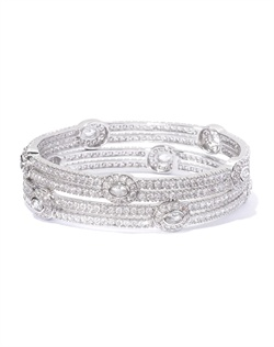 Set of bangles with linear contour defined by round-cut cubic zirconia in a channel setting, punctuated with oval accents. Set in brass with rhodium plating (shown in silver finish).