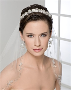 Dimensional tiara of rhinestones and crystals. Shown with a 1 layer elbow length cut edge veil with continuous beaded design and crystal flowers along edge (V7111).