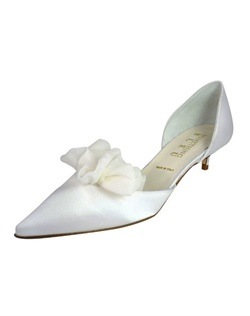 "Lovely closed toe d'Orsay pumps with front ruffle detail. The Chastity by Something Bleu is soft and simple. The design of this classic tapered toe pump is the perfect blend for any plain, ruffled or rouched bridal attire. The comfortable 1 3/4"" heel is great for any bride looking for something low in heel height. Available in white satin with a blue crystal inset in the sole. Not recommended for dyeing."