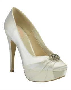 "The Caramel by Pink is sophisticated and fun all in one. The traditional closed toe design is updated for the modern bride with a fabric pleat and rhinestone filigree brooch at the toe. The tall 4 1/4"" heel is balanced in the front by a 1/2"" platform. Available in dyeable white and ivory."