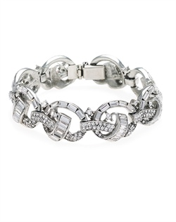Swarovski crystals dance in a silver plated setting that forms an eye-catching interlocking knot motif. With its chic, retro style, this piece will make a striking accent to many different bridal looks.
