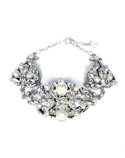 "A stunning statement bracelet with a large rounded filigree brooch accented with Swarovski pearls and various shaped rhinestones. Two smaller components frame this gorgeous centerpiece.Dimensions: 5.5"" L; 2"" extender"