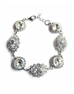 "Shimmering Swarovski brooches alternate with cushion cut crystals accented with a clear bezel. 7"" with 2"" extender"