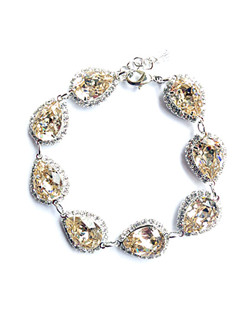 "Silk (champagne) Swarovski crystal teardrops accented with a clear bezel rhinestone chain. 7"" with 2"" extender"