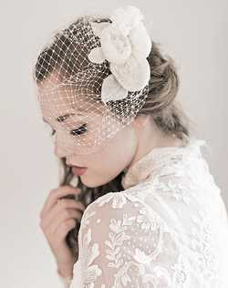 A beautiful way to incorporate a cage veil with an ultra feminine array of flowers. Hand formed silk organza floral blossoms and leaves grace this English netting in beautiful pale ivory.
