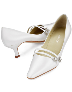 """High fashion meets understated simplicity when you choose this classically styled pump in white or ivory. Champagne is available in limited sizes. Twin straps are accented with rhinestone buckles. Heel measures 1.75"". This shoe is not dyeable."