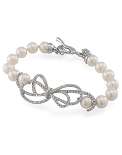 "Simple pearls get the royal treatment with a flourish of crystals tied in a bow. Reminiscent of a Tiffany design, this look is absolutely classic with just the right amount of sparkle. Bracelet measures 7.5"" with a lobster clasp."