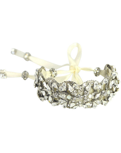 "Make a statement with thisSwarovski crystal encrusted cuff bracelet. The ribbon tie is tipped with crystal accents and gives this bracelet a feminine touch. Bracelet by Maria Elena. Measures 1"" across, 6"" round."