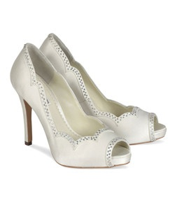 "The Ivory Benjamin Adams Betty shoes are a gorgeous scalloped pump with rhinestone detailing. The classic peep toe design is updated with a beautiful feminine scalloped edging and light rhinestone detail for a touch of sparkle. Heel height measures 4"" with a covered 1/4"" platform front. Available in Ivory Duchess Silk."