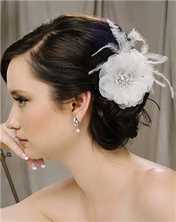 """This little silk flower clip is adorned with a pile of Swarovski stones in the center and a few graceful ostrich plumes. Beautiful! Flower is 3-1/2"""" diameter and available in diamond white and pale ivory."""