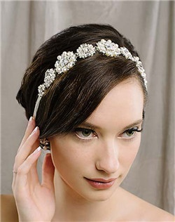 "This stunning hair ribbon is one of our favorites of the new season! The vintage-inspired beadwork glitters in the light thanks to all of the emerald shaped Swarovski stones. And as a big bonus, the piece also be worn as a sash AND a necklace! Available in diamond white and pale ivory, 19"" of beaded secures with satin ties at the back. Approximately 1.25"" wide."