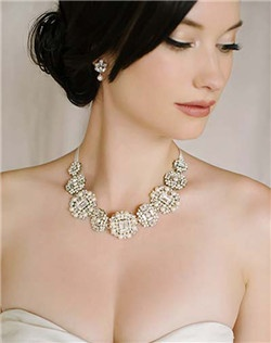 """This stunning necklace is one of our favorites of the new season! The vintage-inspired beadwork glitters in the light thanks to all of the emerald shaped Swarovski stones. And as a big bonus, the piece also be worn as a hair ribbon AND a sash! Available in diamond white and pale ivory, 19"""" of beaded secures with satin ties at the back. Approximately 1.25"""" wide."""