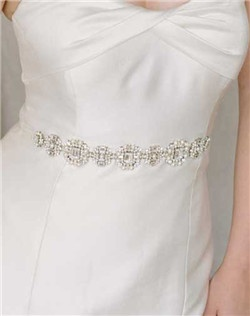 "This stunning sash is one of our favorites of the new season! The vintage-inspired beadwork glitters in the light thanks to all of the emerald shaped Swarovski stones. And as a big bonus, the piece also be worn as a hair ribbon AND a necklace! Available in diamond white and pale ivory, 19"" of beaded secures with satin ties at the back. Approximately 1.25"" wide."