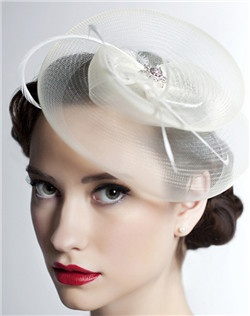 Hats are making a comeback, and with this lovely design we can see why! Horsehair ribbon is coaxed into shape by hand and finished with a glittering Swarovski rhinestone filigree and biot feathers. Available in diamond white, pale ivory, black, aquamarine, amethyst, peacock, moss, sunflower, papaya, sangria, or fuchsia.