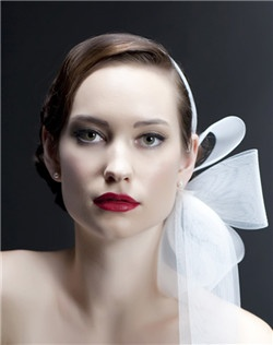 "Made entirely from 3"" wide horsehair ribbon (the same thing gown designers use to stabilize the train of your gown!), this amazing piece forms an avant-garde ""bow"". Accented with chunky SWAROVSKI® crystals.  Band stretches into place on your head. Bow is approximately 9"" x 11"". Available in our standard colors."