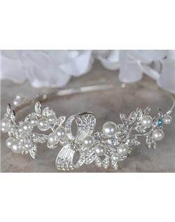 "This side accented bridal headband has an elegant bow design scattered with crystals and hand strung freshwater pearls. It can be made with a tiffany blue crystal incorporated into its design to act as the bride's ""something blue"" item or be made with all clear crystals."