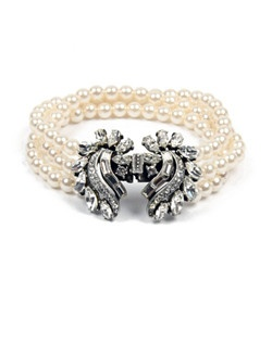 This vintage style pearl and crystal bridal bracelet features four strands of shimmering pearls combined with a bold silver plated Swarovski crystal clasp that shows off a subtle floral motif. This is a timeless piece and is sure to add the perfect elegant accent to any formal event.