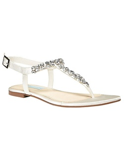 "The Spark by Betsey Johnson is the ultimate bridal sandal. The simple thong design features a rounded toe strap and adjustable ankle strap allow for a comfortable fit. The thong is encrusted with large cut rhinestones that glitter and shine in true Betsey style.  Available in Ivory with a .25"" heel."