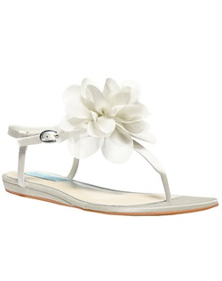 The Iris by Betsey Johnson is a chic thong sandal with gorgeous floral accent at the toe. The simply sandal design lets the flower blossom pop! The Adjustable ankle strap creates a custom fit while the slight 1/4 wedge gives a little lift and support. Available in Ivory satin.