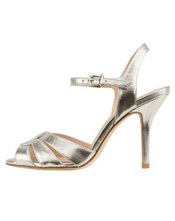 "The Gypsy by Pelle Moda is a classic styles sandal that is simple yet striking. The thick cut Silver Metallic toe straps swirl together creating an interesting effect. The heel measures "". Available in Silver Metallic."