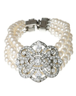 This breathtaking pearl and crystal bridal bracelet from designer Ben Amun will dazzle you with its divine vintage style. Four strands of shimmering pearls combine with a bold silver plated Swarovski crystal brooch that simply radiates Art Deco chic. With its wonderful timeless appeal, this piece is sure to add the perfect elegant accent to any bridal ensemble.