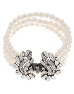 This stunning pearl and crystal bridal bracelet from designer Ben Amun will charm you with its striking vintage style. Four strands of shimmering pearls combine with a bold silver plated Swarovski crystal clasp that shows off a subtle floral motif. With its wonderful timeless appeal, this piece is sure to add the perfect elegant accent to any bridal ensemble.