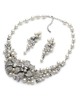 This bridal necklace and earring set is made with sparkling rhinestones and lustrous glass pearls in a rich floral pattern with stunning pave encrusted leaves.