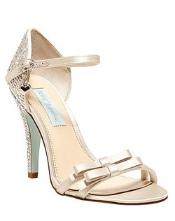 """A magical night lies ahead. The BOW evening sandals by Blue by Betsey Johnson are covered in sparkling rhinestones at back of heel with double bow details across front vamp and feature an adjustable ankle strap.                                                                                                                                               •  Fabric satin/rhinestone upper       •  Strappy upper with bow detail       •  Man-made sole       •  3 ½"""" covered heel"""
